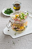 Wholegrain rice salad in a glass jar with salmon, boiled eggs, radishes and cress