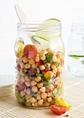 Kichererbsensalat im Glas mit Tomaten, Paprika, roten Zwiebeln, Frühlingszwiebeln, Gewürzen, Limetten, Olivenöl und frischer Petersilie