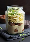 Meatballs and tagliatelle in a glass jar with soy cream and fresh parsley