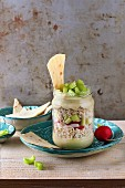 Brown rice salad with houmous, radish and celery in a glass jar