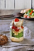 Layered salad in a glass with yellow pea cream, spinach and tomatoes