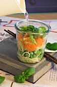 Making Asian noodle soup in a glass: Add hot water and leave to brew