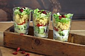 Couscous salad with tomatoes, iceberg lettuce and cranberries in glasses