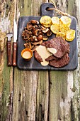 Grilled beef steaks with mushrooms, sauce and fried potatoes on a marble board