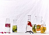 Water infused with fruit, vegetables and flowers in various caraffes and glasses