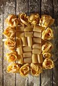 Italienische Pastasorten mit Mehl auf Holztisch