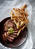 Sliced ribeye steak with herb butter and thin french fries