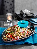 Warm salad with beef strips and vegetables