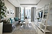 Eleganter Wohnbereich mit Polstercouch, Ghost-Chairs und weißem Leiterregal