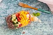 Bunter Salat im Glas mit rotem Quinoa, Gurke, Paprika, Mais, Tomaten, Pecorino und Basilikum, Holzgabel
