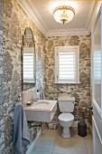 Tapezierter Toilettenraum mit weißem WC, Spülkasten und Waschbecken