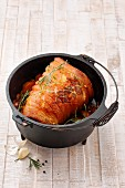 Rolled roasted pork belly in a Dutch oven cooking pot