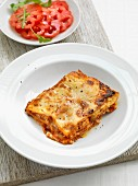 A portion of lasagne with a tomato salad
