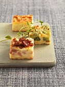 Various quiche appetisers on a chopping board