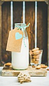 Fresh vegan dairy-free almond milk in glass bottle with craft paper label