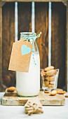 Selbstgemachter veganer Mandeldrink in Glasflasche mit Geschenkanhänger