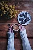 Woman s hands holding a cup of coffee on a rustic wooden table, plate with chocolat coconut bars