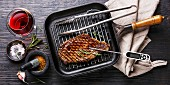Grilled Steak Striploin on pan and meat thermometer on black burned wooden background