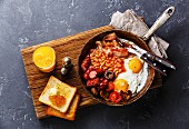 English Breakfast in cooking pan with fried eggs, sausages, bacon, beans, toasts and orange juice on dark stone background
