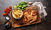 Grilled fried roast Chicken Tabaka and Potato wedges on cutting board on wooden background