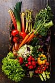 Frisches Gemüse im Korb auf Holzuntergrund (Aufsicht)