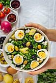 Hände halten eine Schüssel Kartoffelsalat mit Kräutern, Eiern und Oliven