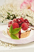 A fresh rasberry tart with a rasberry leaf with rose and hawthorn flowers