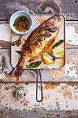 Ganzer gebackener Fisch mit Zitrone und Kapernbutter