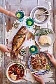 Ganzer gebackener Fisch, Meeresfrüchte-Bouillabaisse, Nudelsalat mit Thunfisch und Fladenbrot