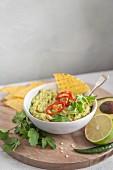 Avocado guacamole in a bowl with coriander and chilli