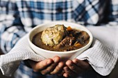 Hands holding a bowl of beef stew