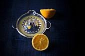 Halbierte Orange mit Saftpresse auf dunklem Untergrund