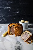 Pork pie (pastry with pork), cut on a marble board