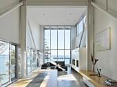 Wohnbereich in experimentellem Strandhaus mit Panoramaverglasung und Meerblick