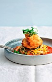 Monkfish piccata on vegetable spaghetti in sweet and sour tomato and pepper sauce