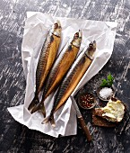Three smoked mackerels on paper with salt and buttered bread