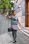 A young Korean taking a selfie with a selfie stick in Bukchon Hanok Village, Seoul, South Korea
