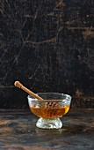 Honey with a honey spoon in a glass bowl in front of a dark background