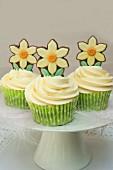 Ostercupcakes auf Kuchenständer mit Federn und Schokoladen-Narzissen