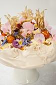 Meringue-Torte garniert mit Blüten und karamelisierten Physalis