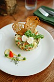 A vegetable tart garnished with quail's egg and crunchy bread chips