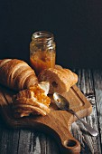 Croissants and marmalade on a chopping board