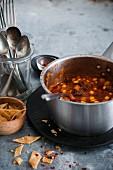 Veganes Chili mit Bohnen, Mais und Kichererbsen im Kochtopf (Mexiko)