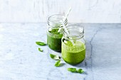An apple and spinach smoothie and an apple and kale smoothie with basil