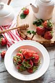 Frische Erdbeeren, Honig und Teekanne