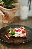 A slice of raspberry tart with fresh mint