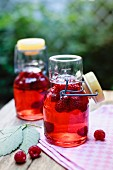 Homemade raspberry vinegar in flip-top bottles on a table outdoors