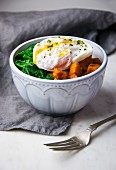 A breakfast bowl with poached egg, sauteed greens and sweet potatoes