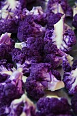 A close up view of chopped purple cauliflower florets on roasting pan