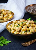 Chickpeas marinated in olive oil and fresh herbs plated in gold bowls